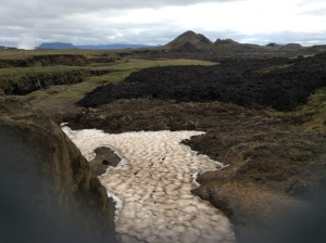 Black lava from the Krafla Fires (1984) over the grey Myvatn Fires lava (1724-29) next to snow. Fracture crack to the left.
